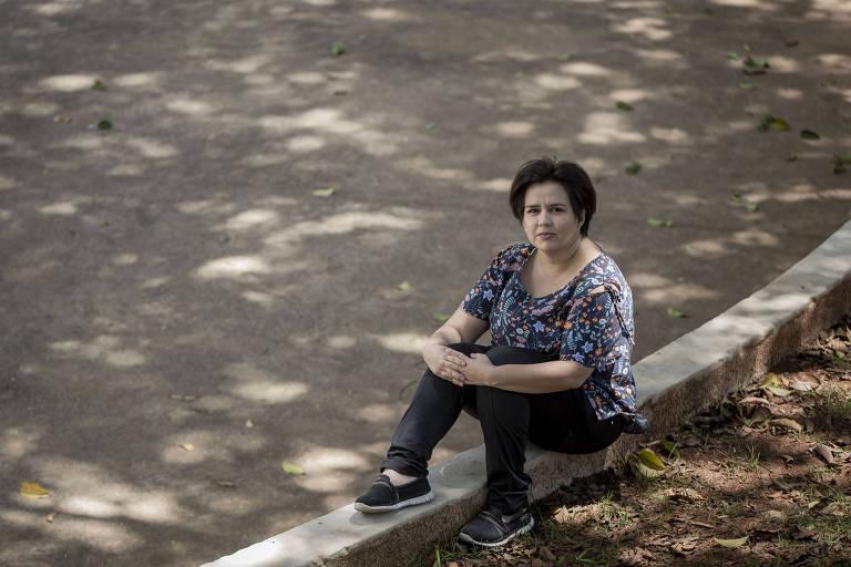 Mulher sentada em uma mureta baixa, perto de um chão de cimento