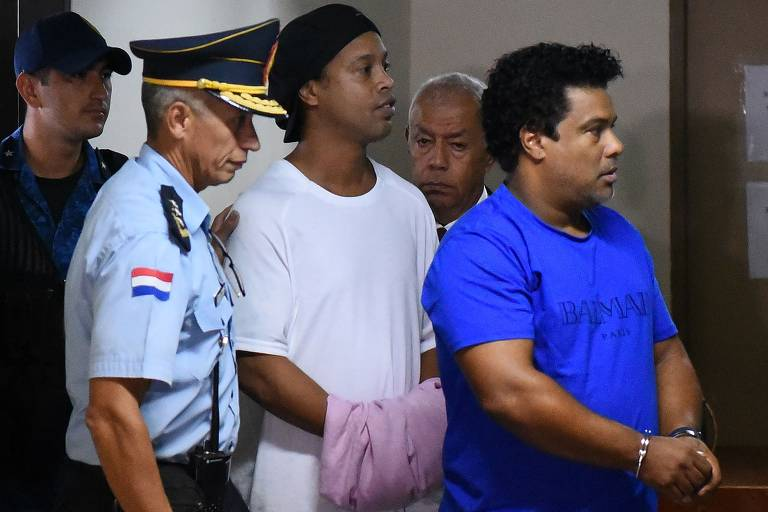 Dois homens algemados ao lado de policial