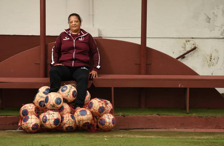 Mulher de moletom vinho sentada em banco, com sacola cheia de bolas de futebol aos seus pés