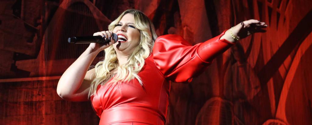 A cantora Marília Mendonça em show com um macacão de couro vermelho, que tem apenas um manga comprida e bufante