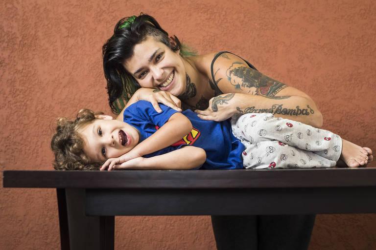 Retrato da mãe com o filho, que está deitado em cima de uma mesa. Os dois sorriem para a foto