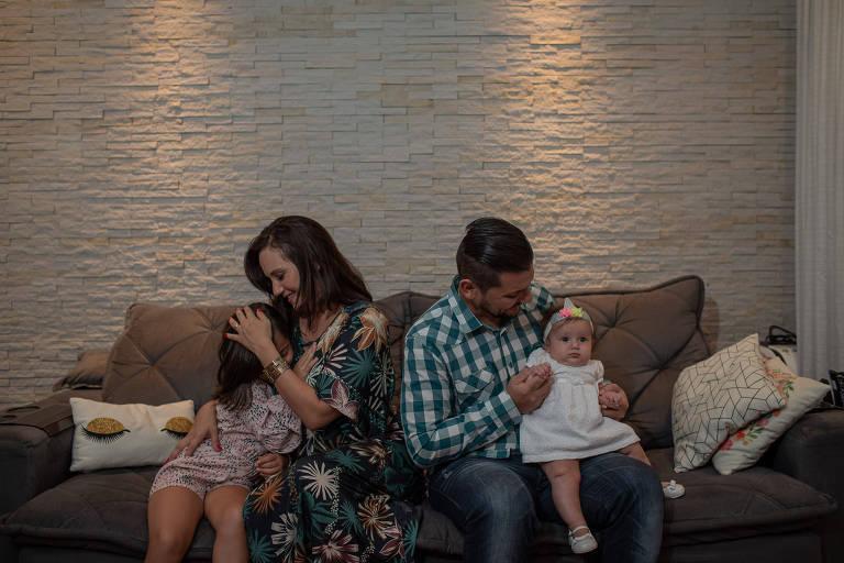 Retrato do casal com cada filho no colo sentado em um sofá; os pais fazem carinho nas filhas