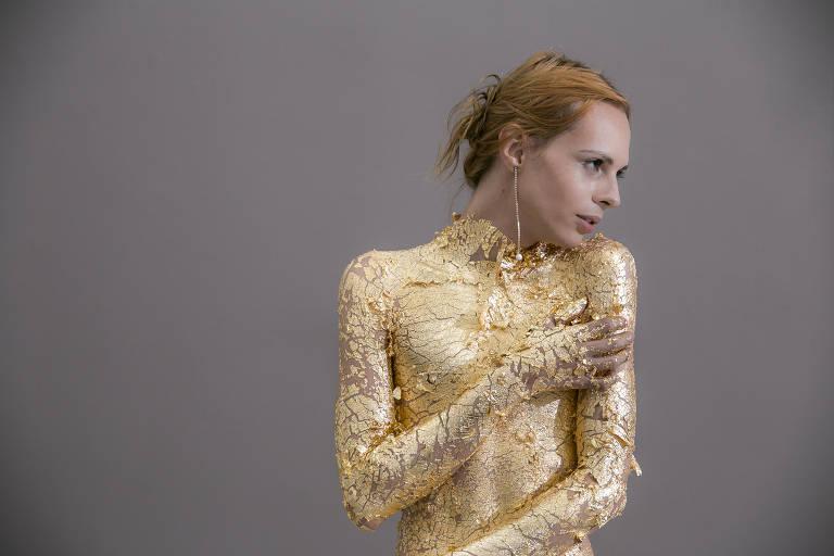 mulher trans coberta com folhas de ouro