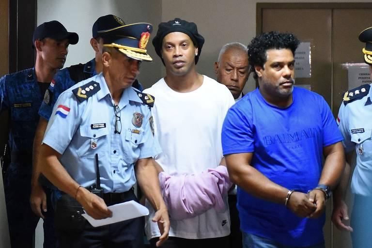 Ronaldinho (de branco) e Assis (de azul) ao serem presos em Assunção, no Paraguai