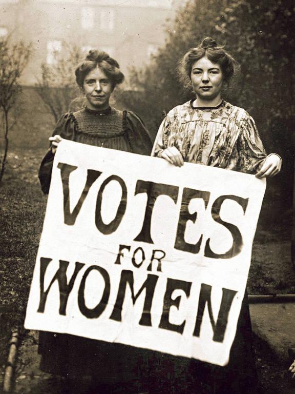 Sufragistas fazem campanha no Reino Unido  As sufragistas inglesas Annie Kenney e Christabel Pankhurst seguram cartaz com o slogan 'Vote for Women', criado por elas e adotado pelo movimento em favor do voto feminino; elas faziam parte da WSPU, organização militante que lutou pelo sufrágio feminino no Reino Unido entre 1903 e 1917