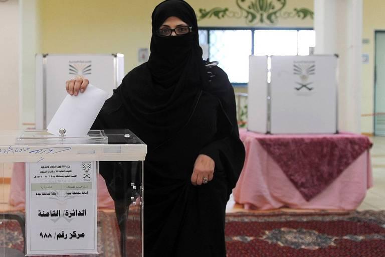 Mulheres passam a votar na Arábia Saudita  Eleitora deposita cédula em urna durante eleições na Arábia Saudita em 2015, quando as mulheres foram autorizadas a votar pela primeira vez na história do país, um reino islâmico ultraconservador