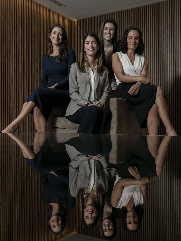 Quatro mulheres aparecerem sentadas na foto, sua imagem está refletiva em uma mesa de vidro