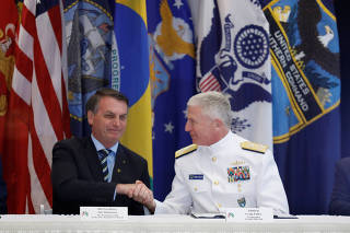 Brazilian President Jair Bolsonaro and Commander of the U.S. Southern Command Admiral Craig S. Faller shake hands during an agreement signing ceremony, in Miami