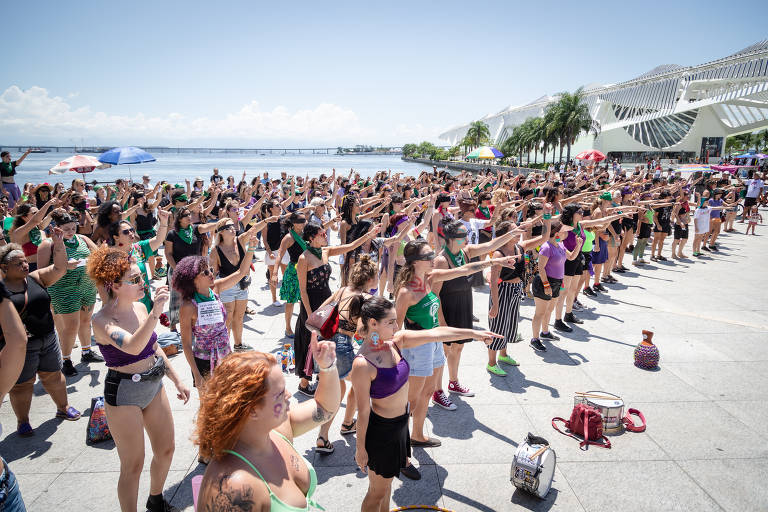 Centenas de mulheres fazem performance coletiva - elas vestem as cores roxo e verde e apontam para a frente, enfileiradas na praça Mauá
