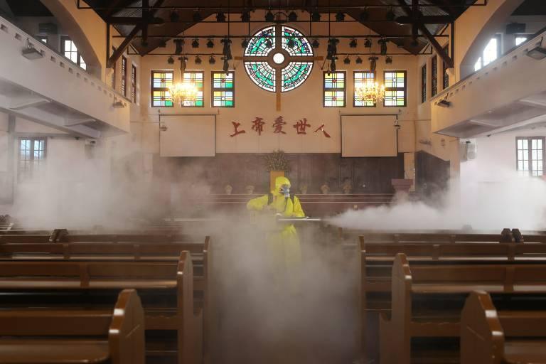 Retrato de uma igreja com apenas um homem dentro. ele usa uma roupa de proteção e borrifa uma fumaça branca
