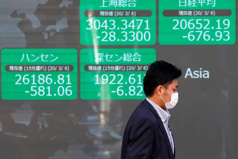 Homem usando máscara passa em frente a painel eletrônico em Tóquio que mostra o desempenho das Bolsas asiáticas