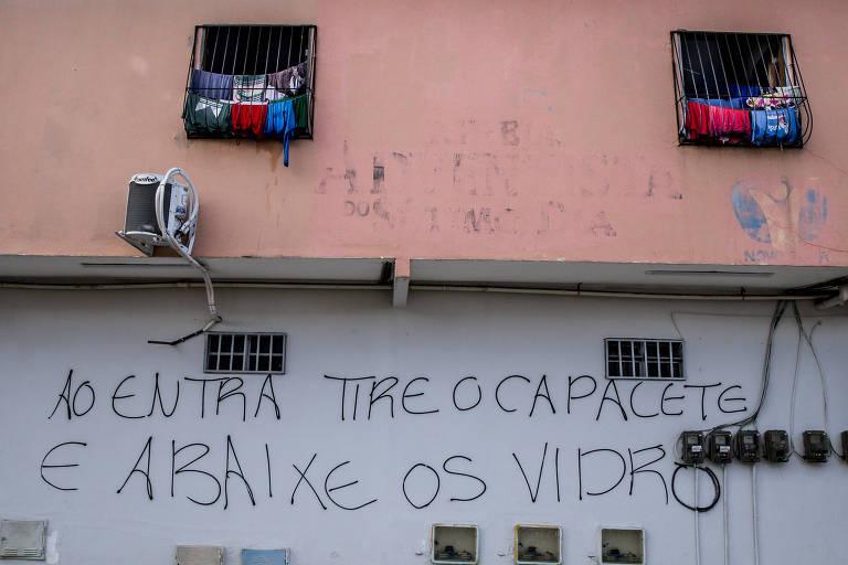 """Prédio de dois andares pintado de cor de rosa no qual roupas pendem das duas janela para secar ostenta  a pichação, no piso inferior: """"Ao entra tire o capacete e abaixe os vidro"""""""