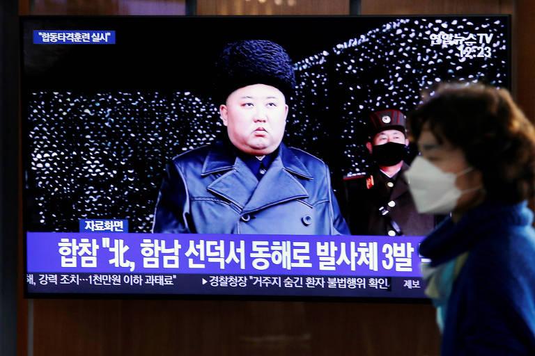 Em uma televisão, o ditador da Coreia do Norte, Kim Jong Un, aparece de jaqueta preta e gorro. À frente, desfocada, uma mulher passa com uma máscara hospitalar