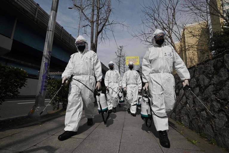 Soldados coreanos usam macacão branco e máquinas de spray para desinfetar ruas