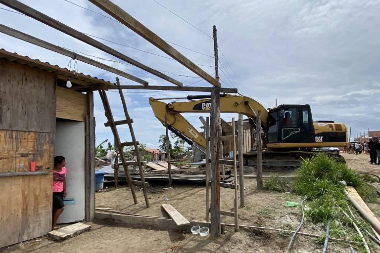 Mulher vestida de rosa observa na porta de barraco de madeira em chão de terra batida uma escavadeira que remove partes de barracos a cerca de 20 metros de distãncia