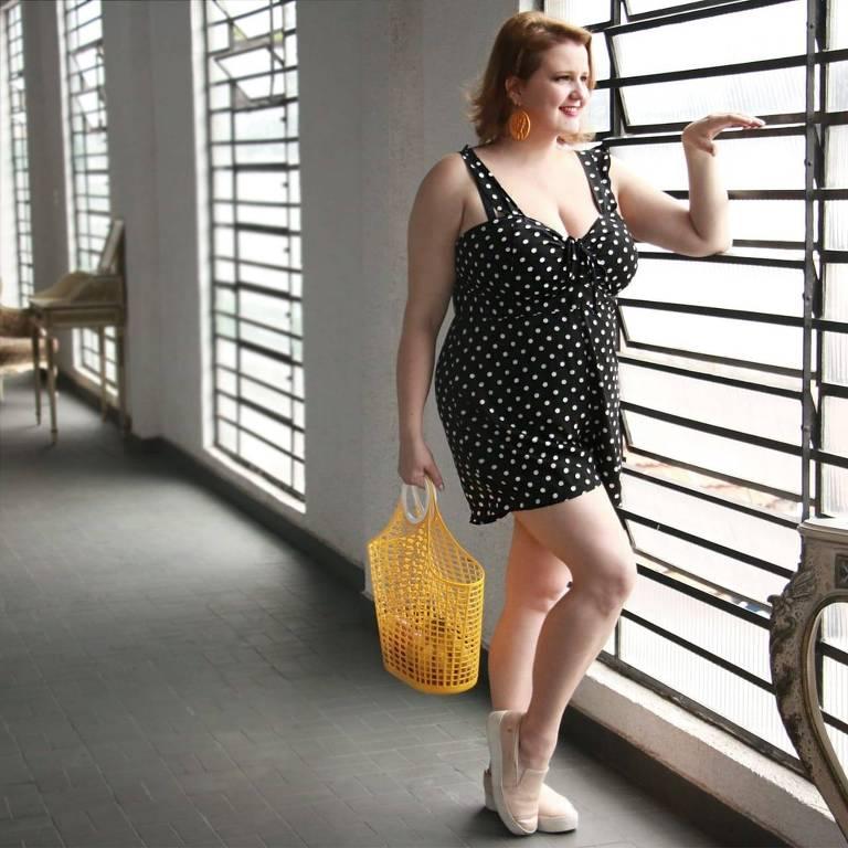 Mulher usando vestido preto olhando para janela