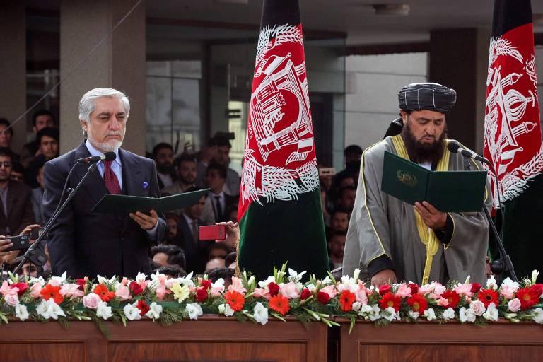 O ex-primeiro-ministro do Afeganistão Abdullah Abdullah, à esquerda, faz juramento ao lado do clérigo Shahzada Shahidwhile em cerimônia paralela de posse em Cabul