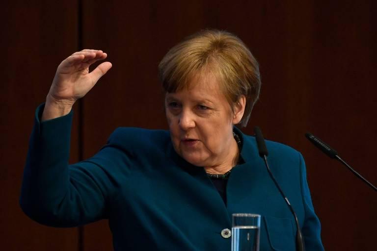 De roupa verde escuro, Merkel gesticula com a mão direita