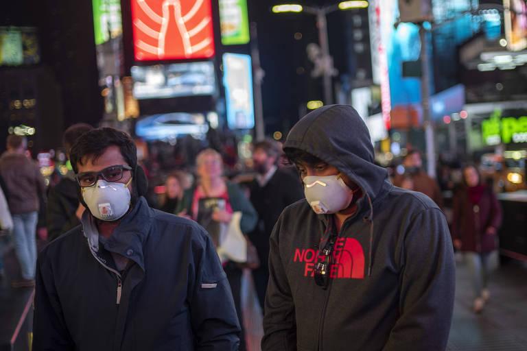Turistas usam máscaras na Times Square em Nova York, nos Estados Unidos. País já tem 22 mortos e mais de 400 infectados