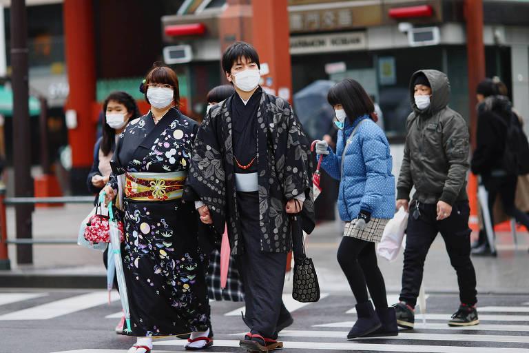 Pessoas usam máscaras ao andar pelas ruas de Tóquio, cidade que sediará os Jogos Olímpicos de 2020