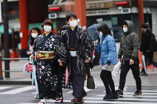 A couple wearing protective face masks, following an outbreak of the coronavirus disease (COVID-19), visits Asakusa neighbourhood in Tokyo