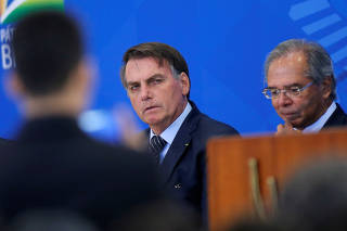 Brazil's President Jair Bolsonaro looks on next to Brazil's Economy Minister Paulo Guedes during a launch ceremony of real estate credit incentive program of the Caixa Economica Federal Bank at the Planalto Palace in Brasilia