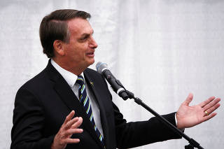 Brazilian President Jair Bolsonaro gestures as he speaks during a meeting with the Brazilian community at The Miami Dade College Auditorium, in Miami