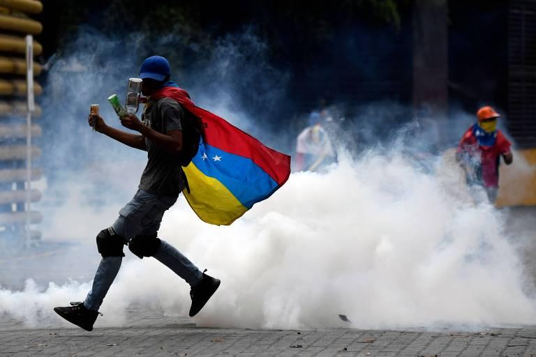 Apoiador de Juan Guiadó devolve bomba de gás lacrimogêneo lançada pela polícia em Caracas