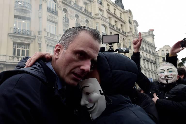 Javier Ortega Smith, deputado do Vox, abraça manifestante com máscara de Guy Fawkes durante protesto por aumento de salários para policiais em Madri