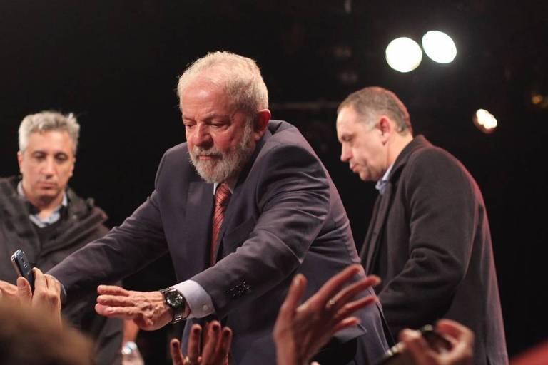 Lula estende as mãos para o público e cumprimenta algumas pessoas