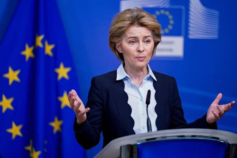 com uma bandeira da união europeia (azul com um círuclo de estrelas amarelas) ao fundo, a política gesticula, de blusa azul clara e casaco preto