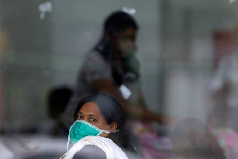 Mulher usando máscara de proteção no rosto é vista atrás de vidraça; ao fundo, há uma imagem desfocada de outra mulher de máscara