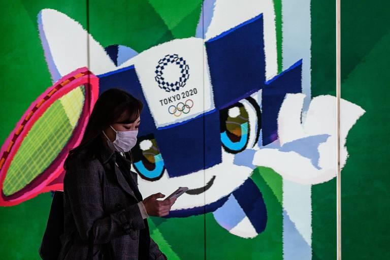 Mulher usa máscara em frente a pôster com a mascote da Olimpíada Miraitowa