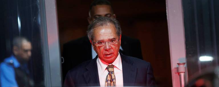 Paulo Guedes caminha até um carro, que tem a porta de trás aberta; o ministro usa óculos de grau retangular, veste um terno preto, camisa branca e gravata com estampa marrom e amarelo escuro