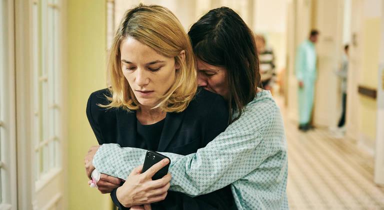 Lola está sendo abraçada pela irmã. Ela é loira e veste preto e sua irmã tem cabelo preto e veste um roupão de paciente com bolinhas pretas. A cena acontece em um hospital.