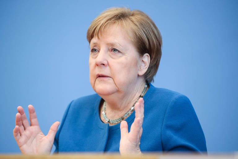 Merkel é vista falando, com as mãos entreabertas, contra um fundo azul