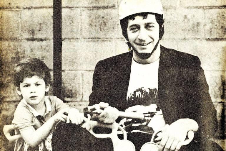 Glauco e o filho pequeno estão lado a lado, cada um sentado e um carrinho tico tico