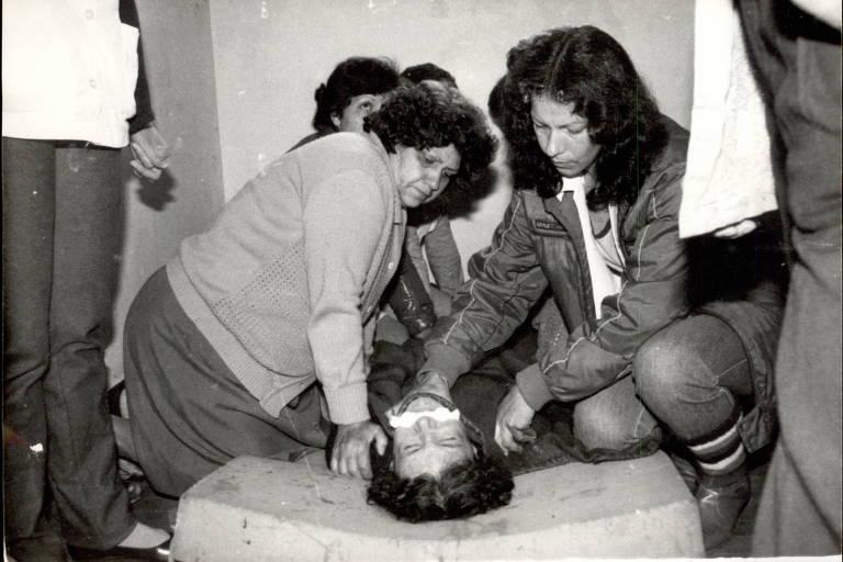 Mulher está amordaçada e deitada em um colchão enquanto outras a seguram
