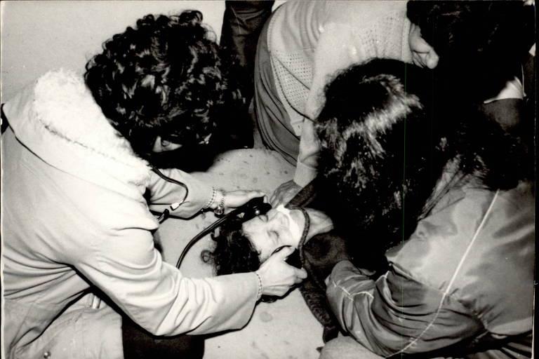 Várias pessoas seguram uma mulher em um colchão, enquanto eletrodos são colocados em suas têmporas