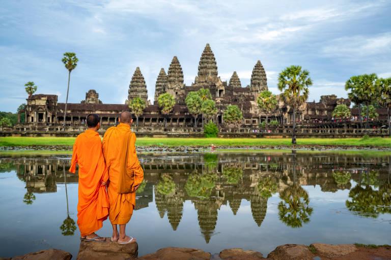 Monges observam as ruínas de Angkor Wat, cidade de templos construída no interior do Camboja