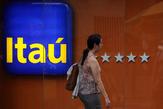 FILE PHOTO: A woman walks past an Itau branch in Rio de Janeiro