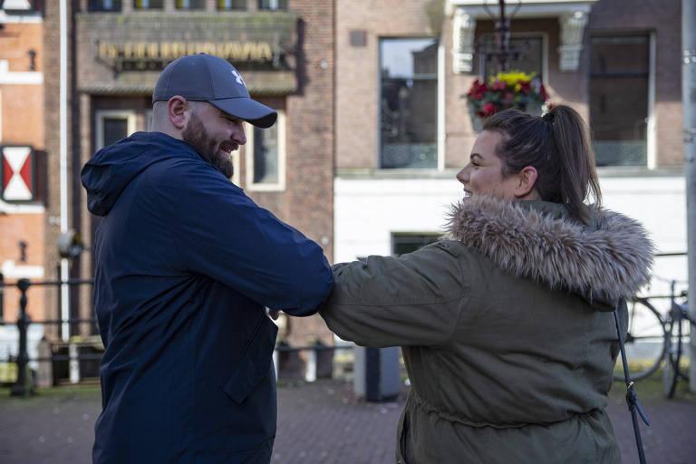 homem de roupa preta toca cotovelo no cotovelo de moça de casaco bege