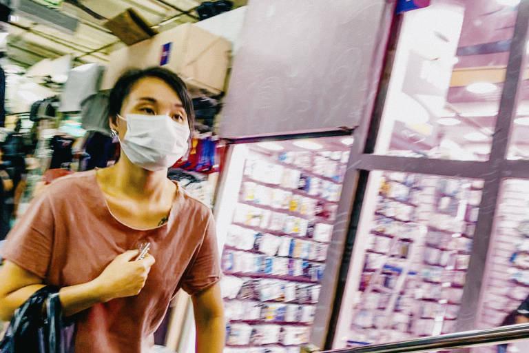No centro de São Paulo, pessoas usam máscara em galerias que vendem produtos populares; preços aumentaram por causa da alta do dólar
