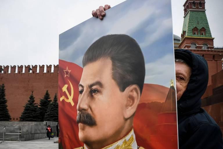 Apoiador do partido comunista russo em Moscou carrega retrato de Stálin durante comemorações de 67 anos de morte do líder soviético