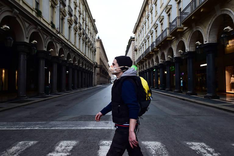 Pessoa de máscara passa por rua deserta em Turim, na Itália, em meio a casos de coronavírus no país
