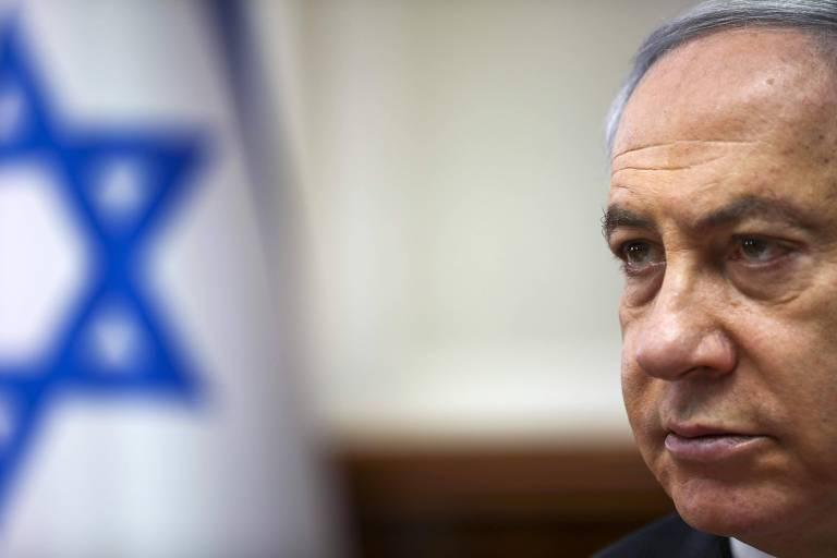 Homem branco com cara séria e bandeira de Israel (estrela de davi azul sob fundo branco) ao fundo