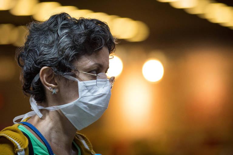 Mulher usa mascara de proteção no aeroporto de Guarulhos