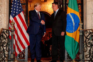 U.S. President Trump shakes hands with Brazil's President Bolsonaro at Mar-a-Lago residency in Palm Beach