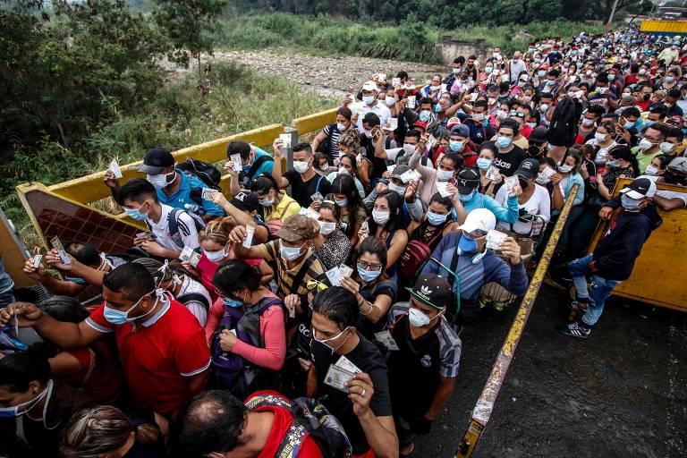 Multidão de imigrantes com máscaras cirúrgicas em ponte