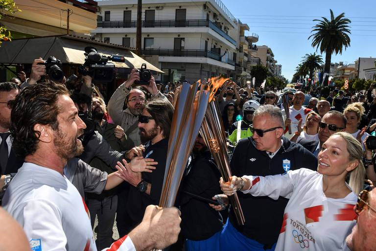 O ator Gerard Butler passa a chama olímpica durante revezamento da tocha em Esparta